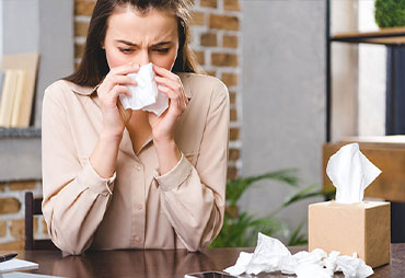 Woman suffering from horrible alergies at work