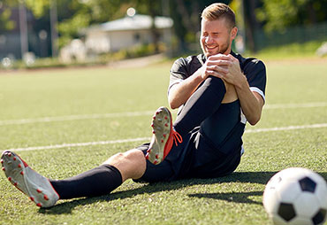 Soccer player suffering with sports injury