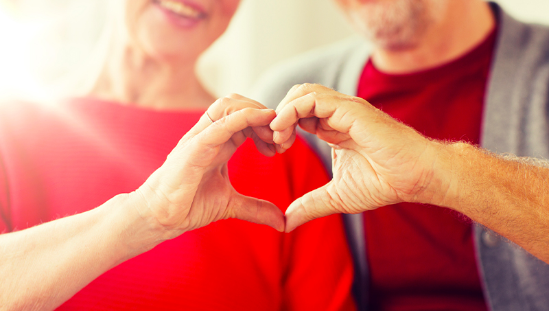 Mature couple holding hands in heart shape