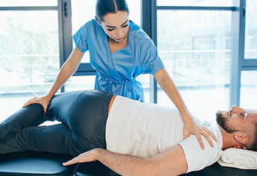 Chiropractor adjusting patient with sciatica